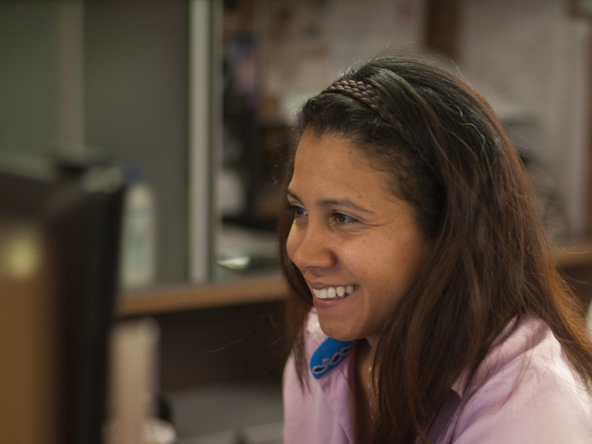 A woman smiles at her desk