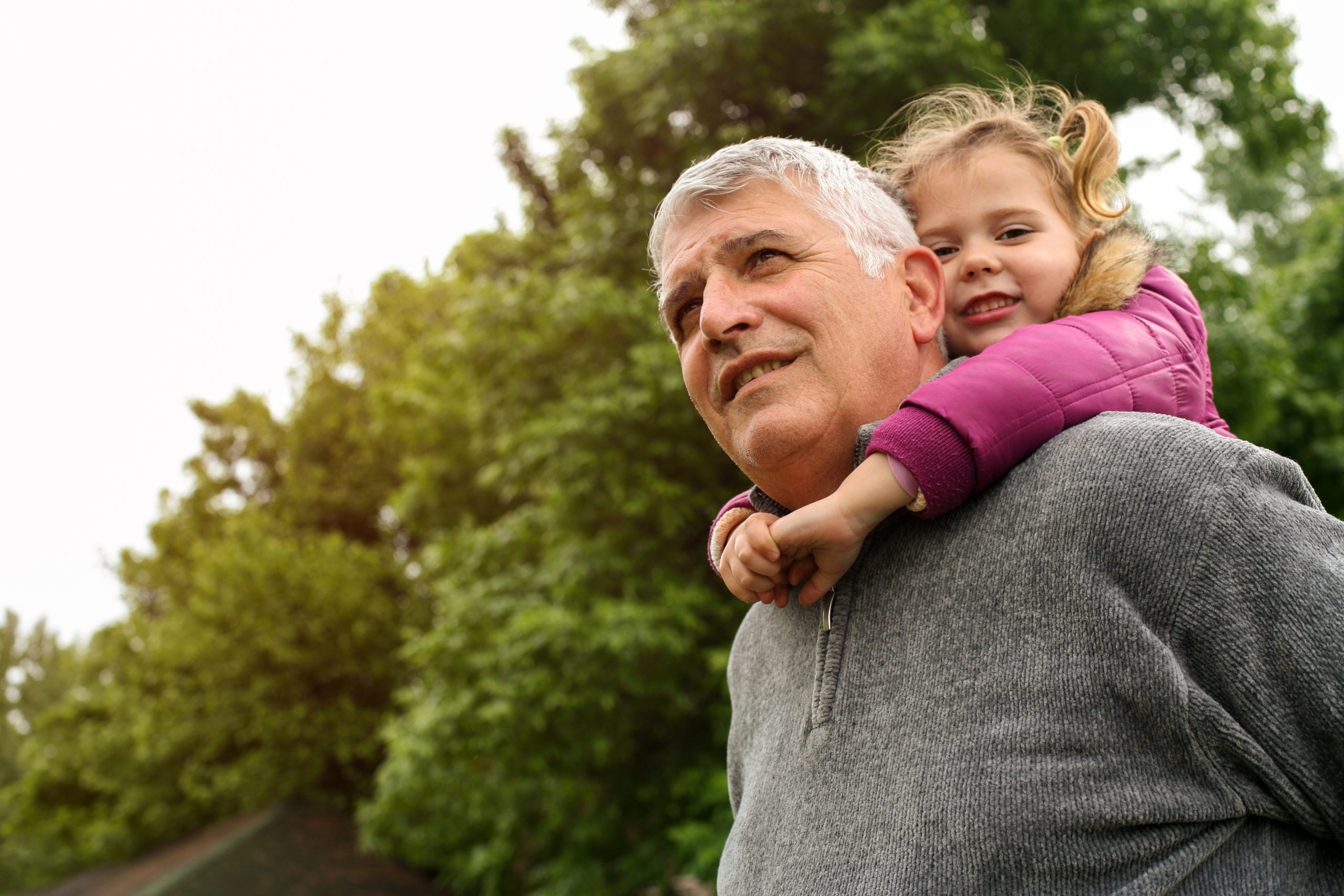 Grandfather with his granddaughter in the park. Little girl looking at camera.