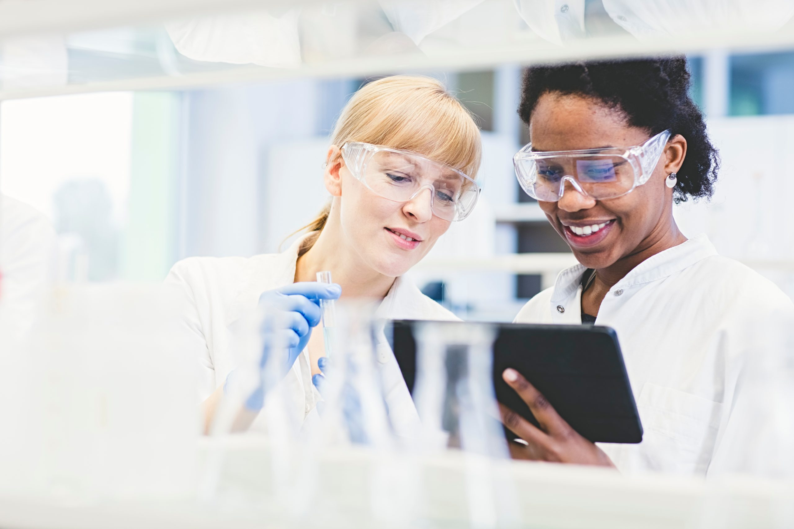 Two smiling female scientists in a lab observing a tablet