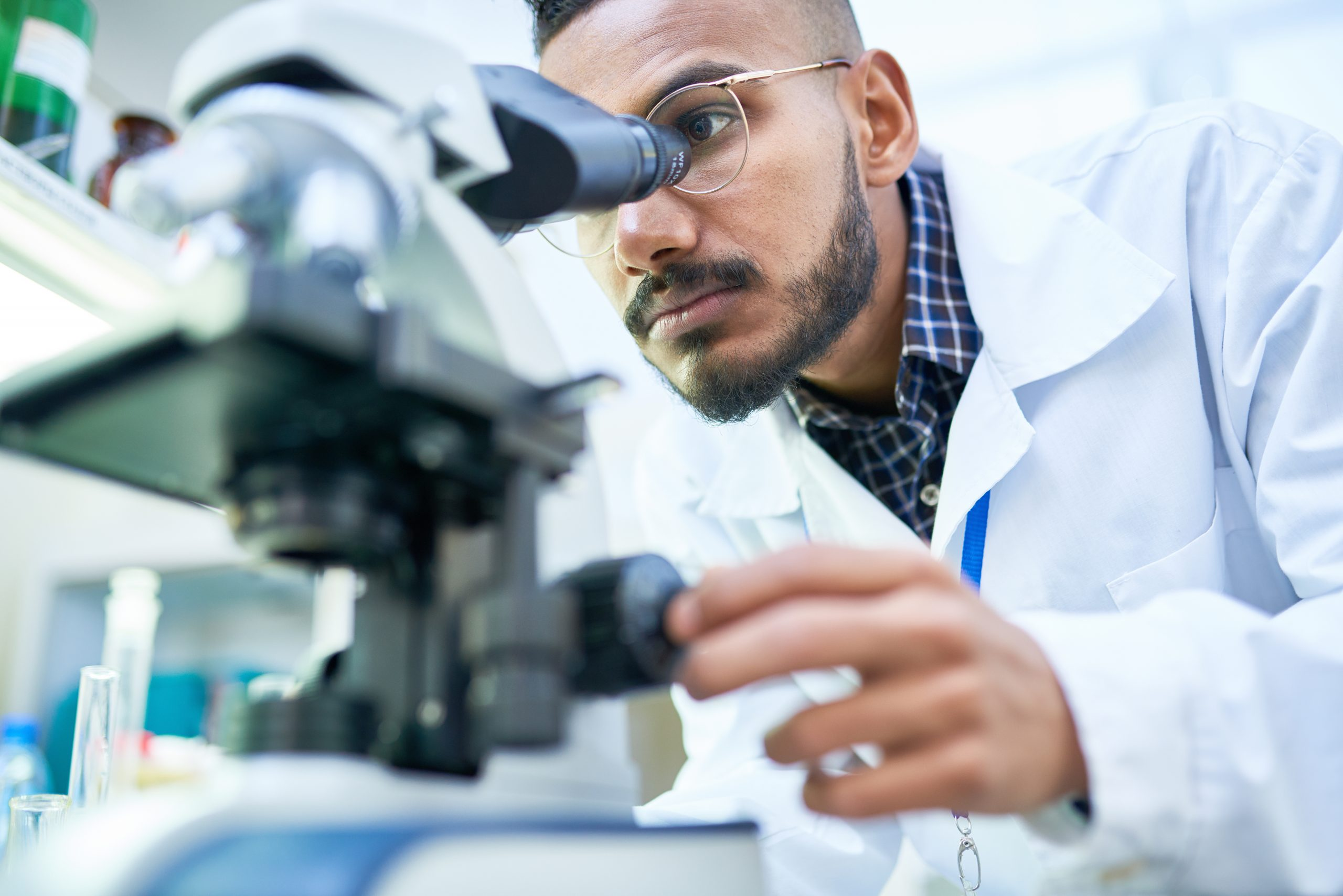 Young male scientist looking in microscope while working on medical research in a laboratory