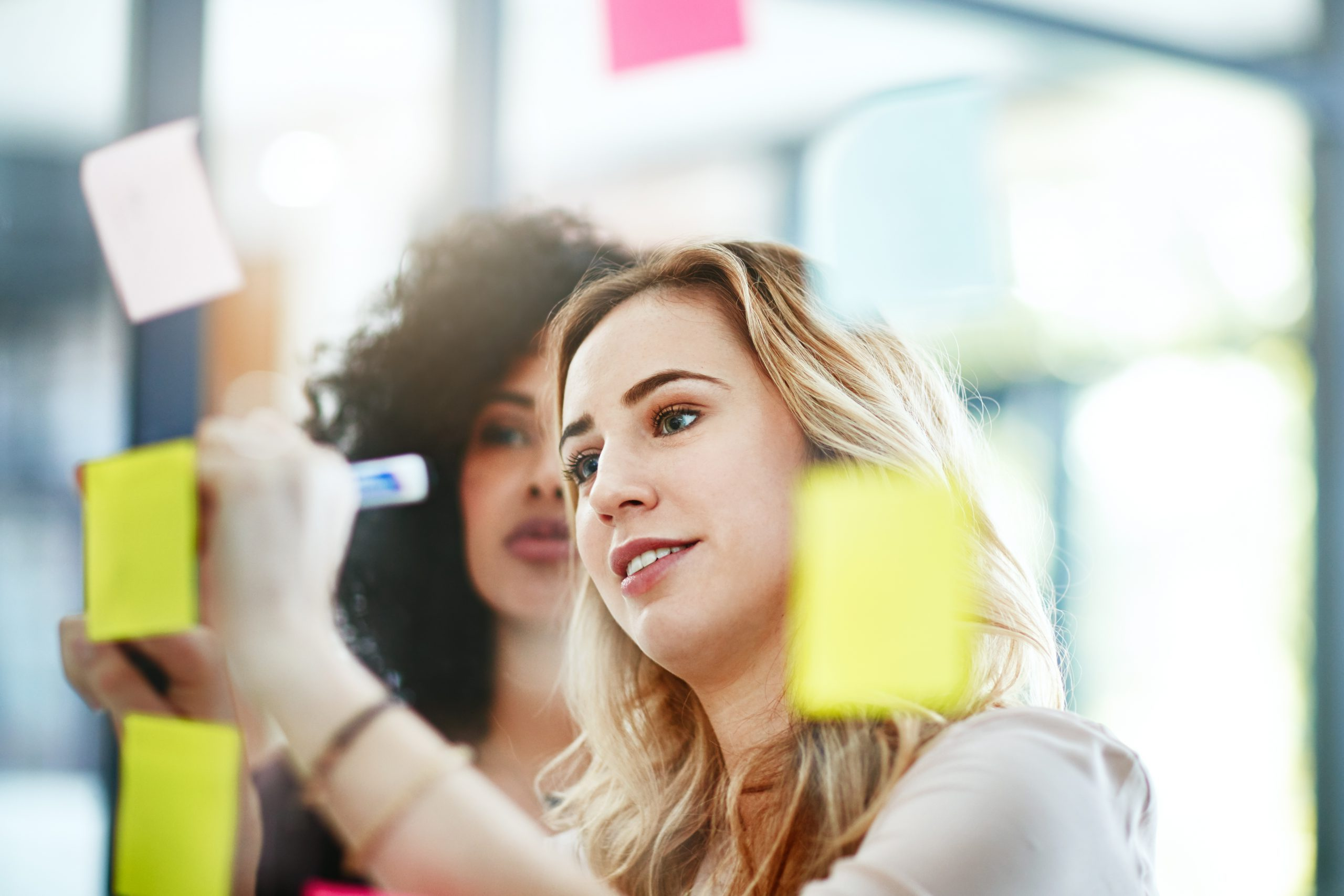 A woman looks on as another woman writes on a sticky note