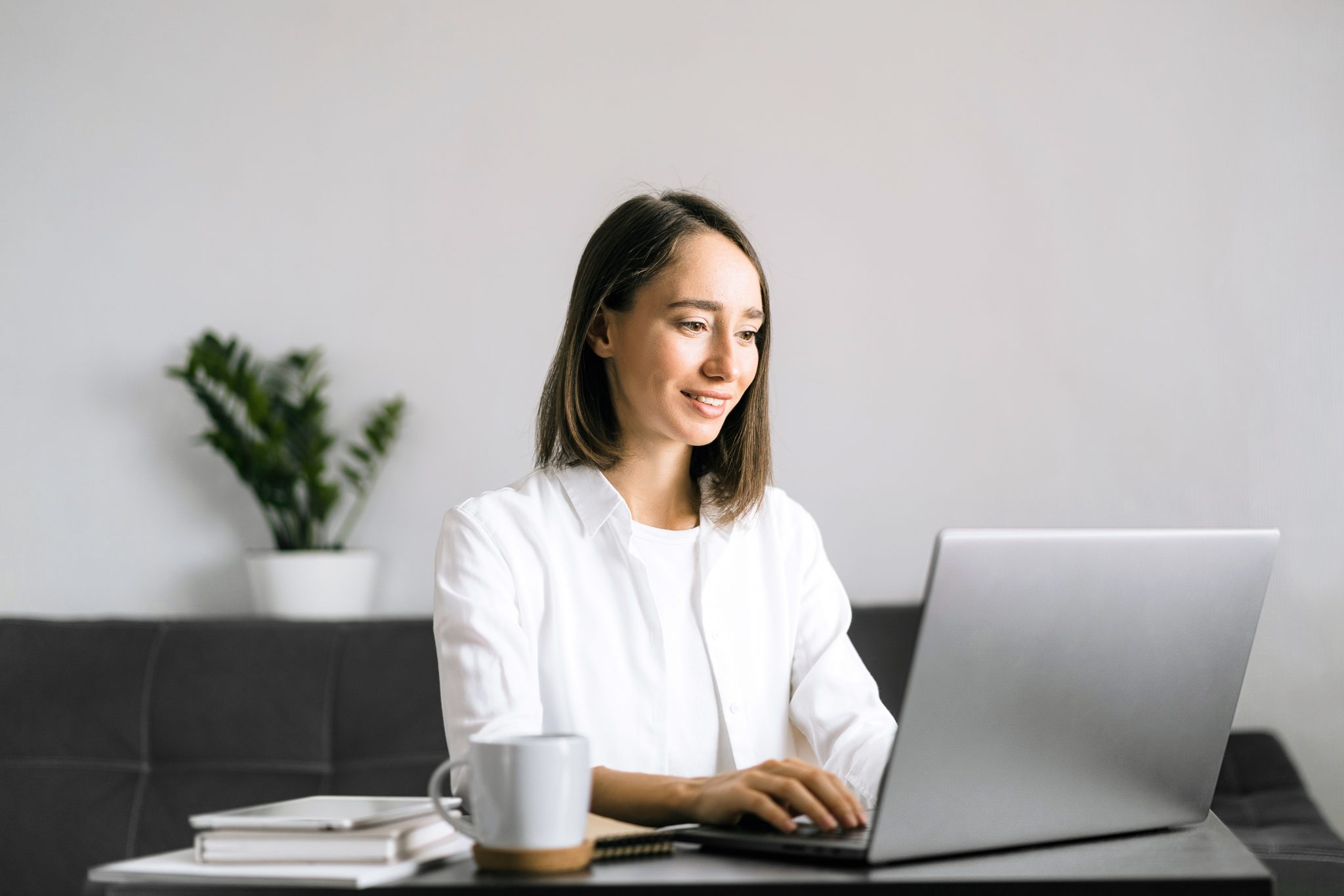 Young woman sitting at the table and using laptop.