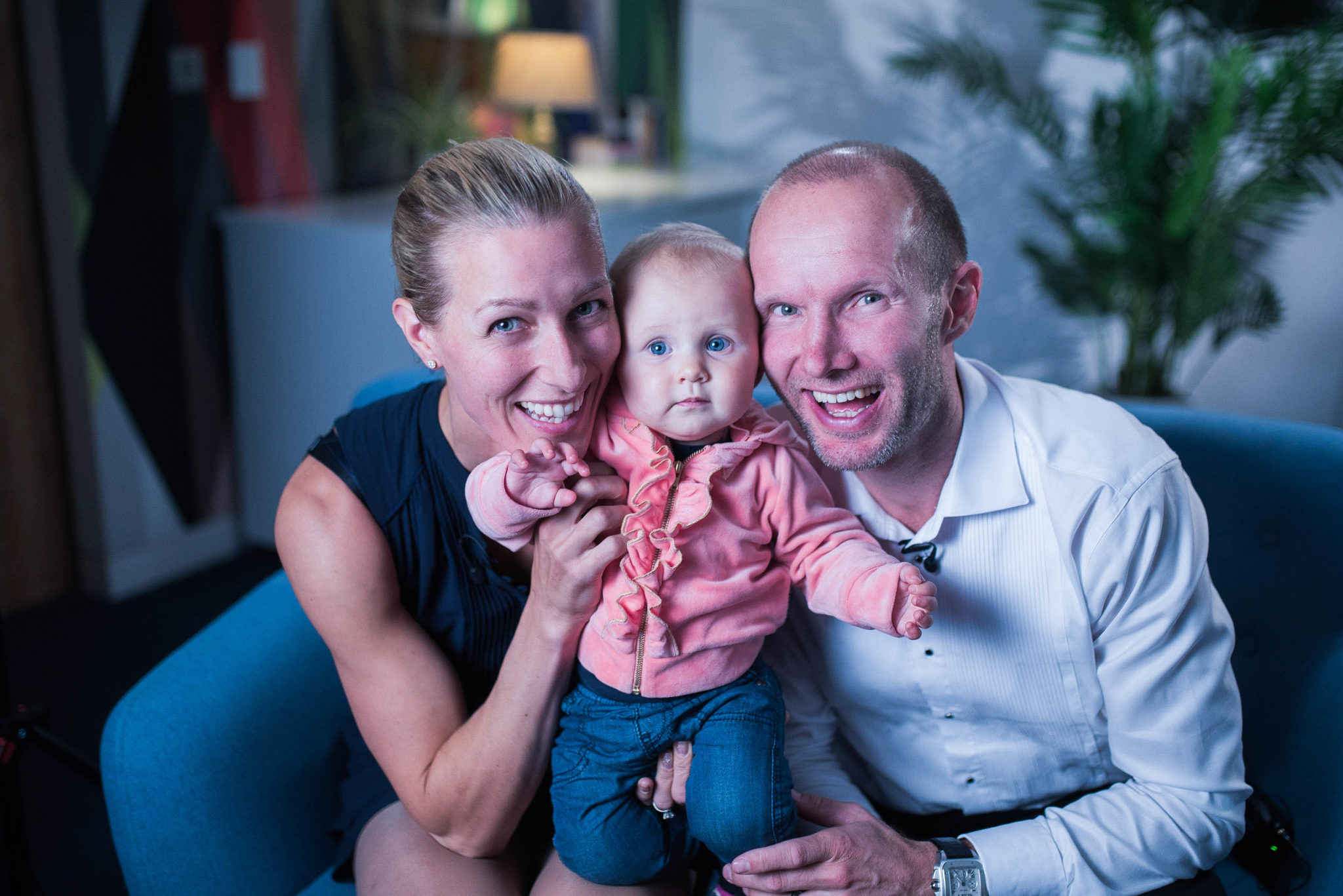 A smiling couple seated with their baby son between them