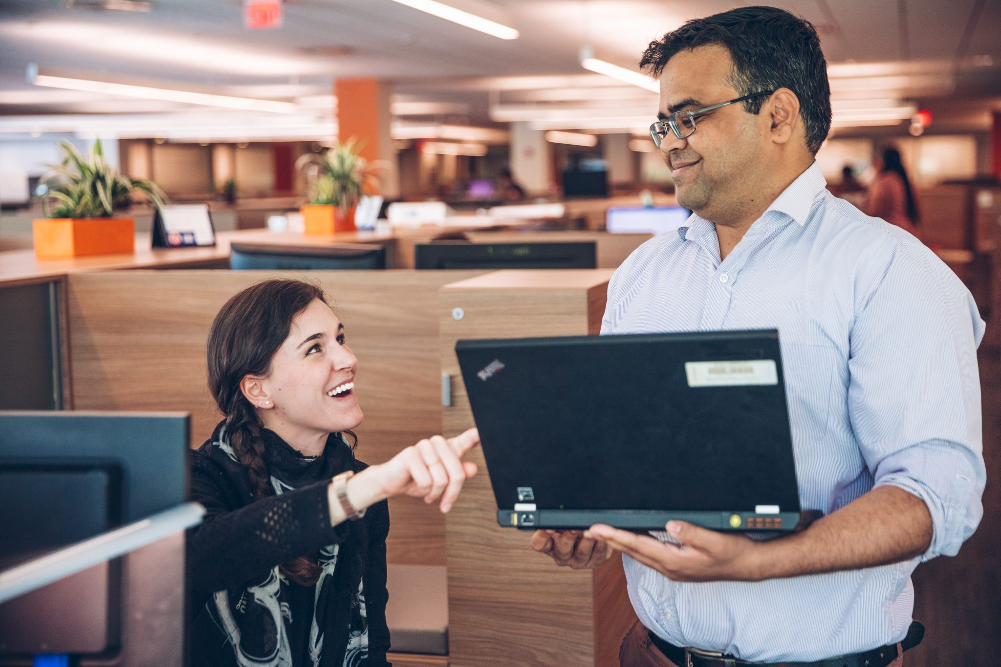 Coworkers, a seated woman and a standing man, in cheerful discussion
