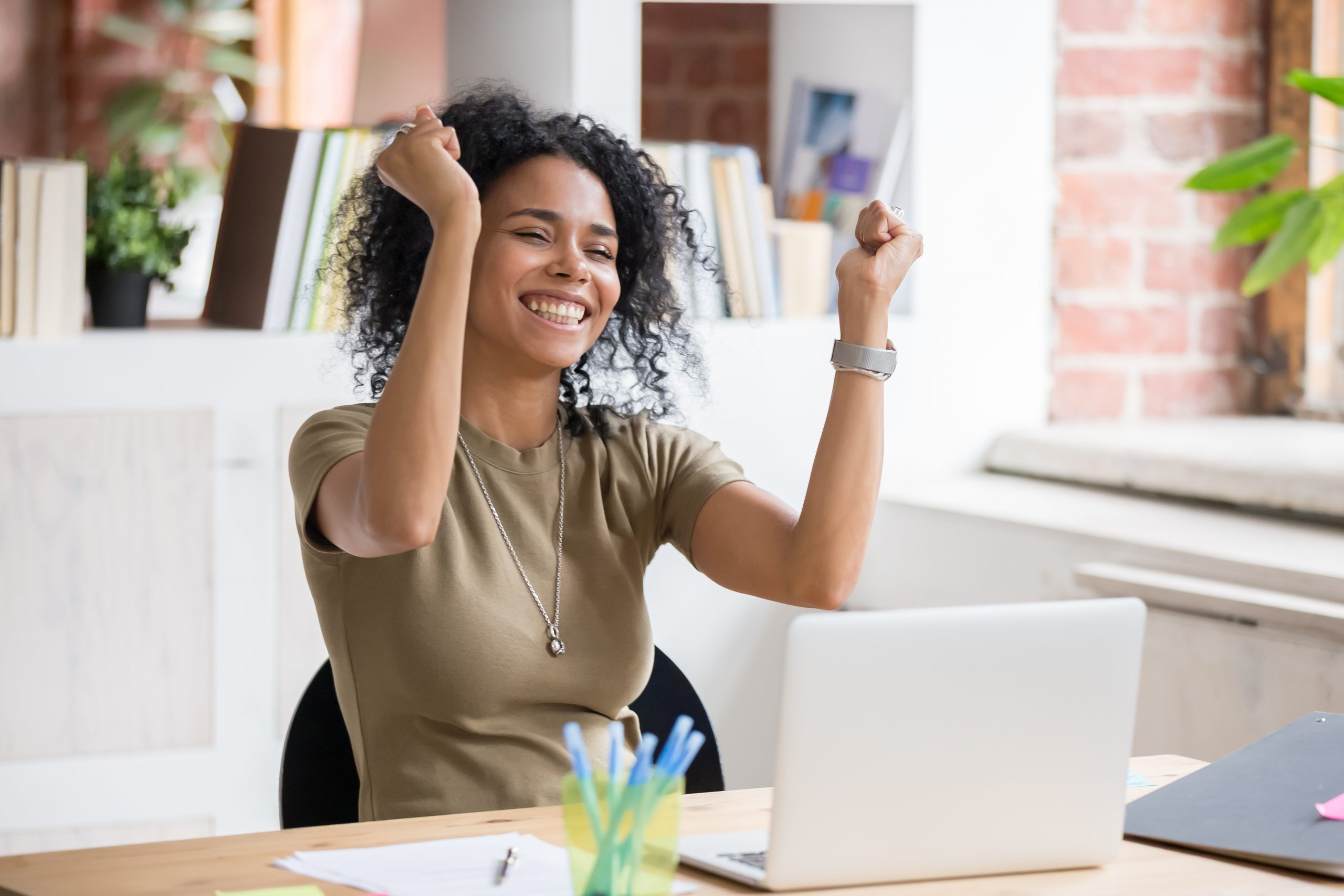 A young woman seated at a computer in a modern office setting raises her hands in celebration