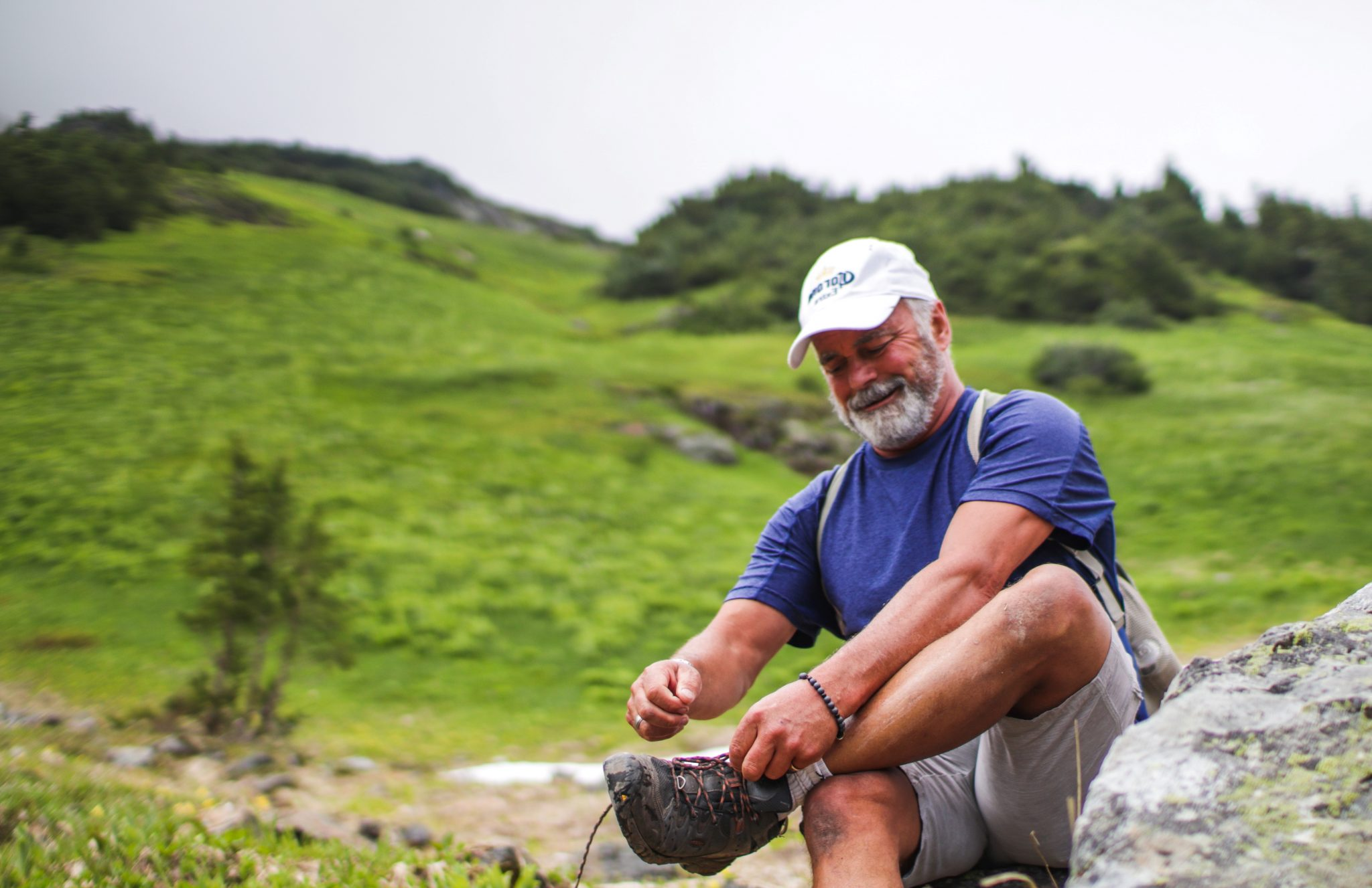 A middle aged man pauses to tie his shoe on a hike in a hilly, green landscape