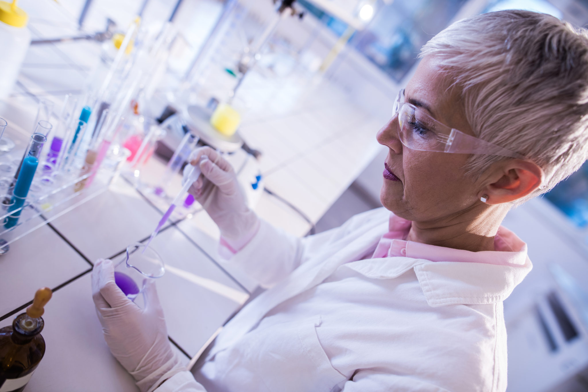 Mature female chemist working on scientific experiment in the lab